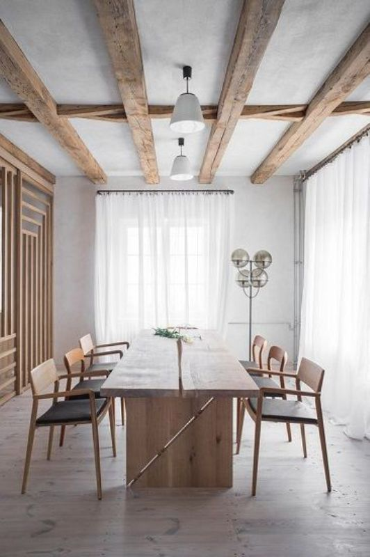 a lovely Japandi dining room with wooden beams, a storage unit clad with wooden slabs, a wooden dining table and black chairs