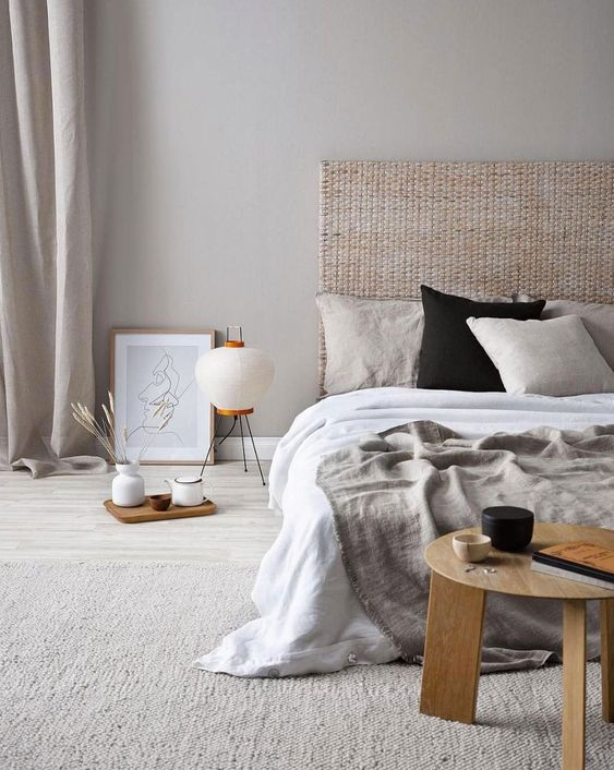 a lovely and welcoming Japandi bedroom done in neutrals, with a bed with a woven headboard, neutral bedding, a light-stained table and a floor lamp