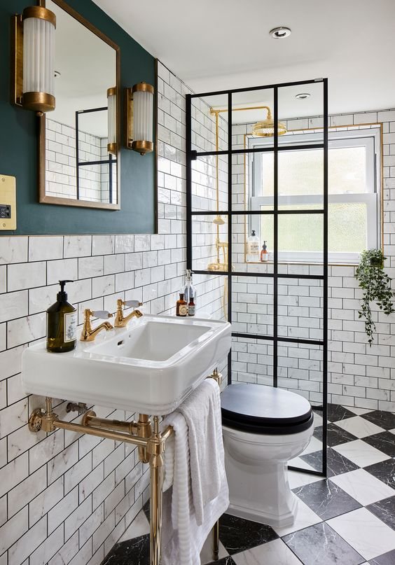 a lovely art deco bathroom with white subway tiles, a console sink, a shower space with a glass wall, brass touches for maximal elegance