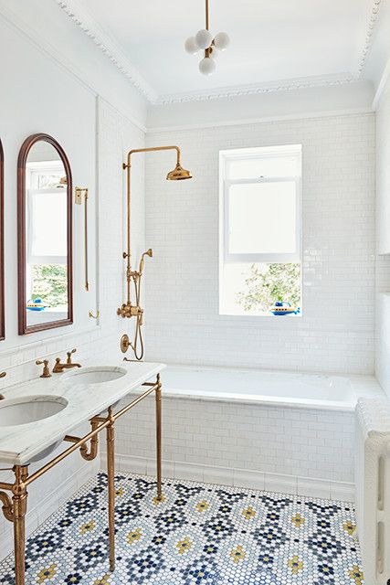a lovely bathroom with penny tiles on the floor, a tub clad with white subway tiles, a double console sink, arched mirrors and brass and copper touches