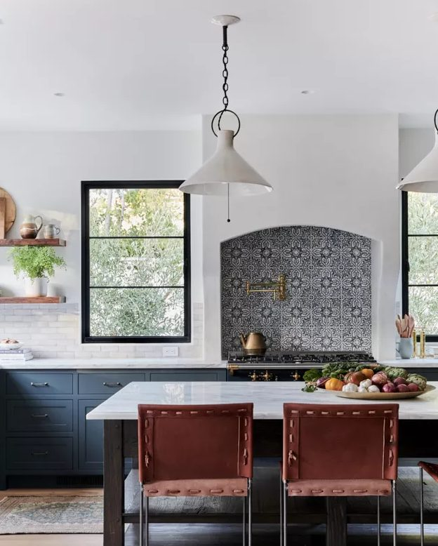 a lovely blue kitchen with shaker cabinets, white countertops and white tiles plus a gorgeous Moroccan tile backsplash over the cooker