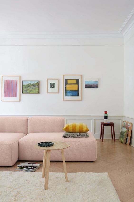a lovely bright living room with a pink low sofa, a colorful gallery wall, panelling, a round table and a creamy rug is cool