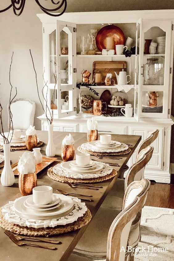 a lovely dining room accented with copper mugs and a hammered copper plate in the buffet is a very pretty and bright idea for a farmhouse space