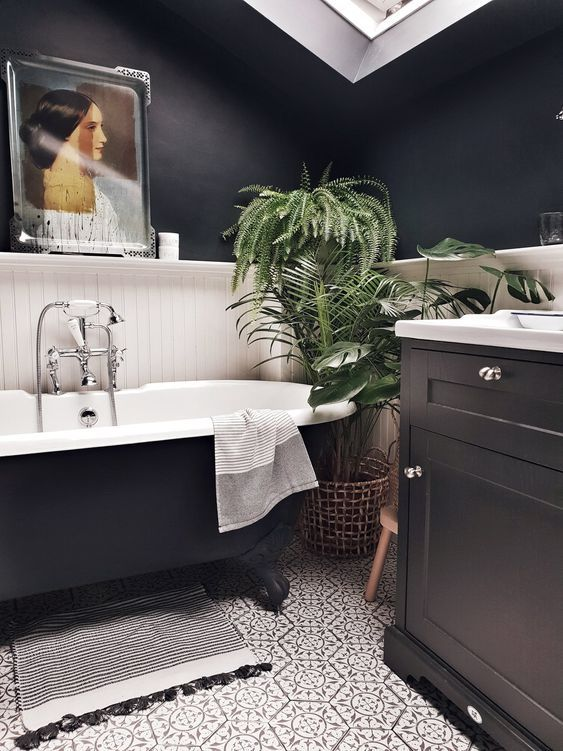 a lovely modern bathroom with black walls, white planks, a black vanity, a black tub, patterned tiles, a skylight and an artwork