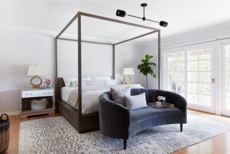 a lovely modern bedroom with a canopy bed, a grey curved sofa, matching nightstands, table lamps and a chic chandelier