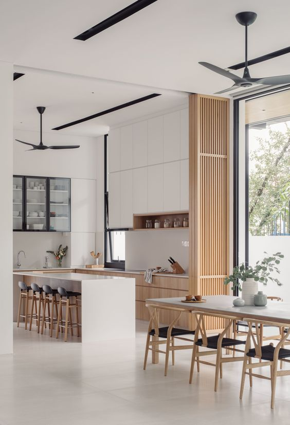 a lovely neutral Japandi interior with sleek white and light-stained cabinets, with a white kitchen island, a wooden slab divider, a laconic dining set