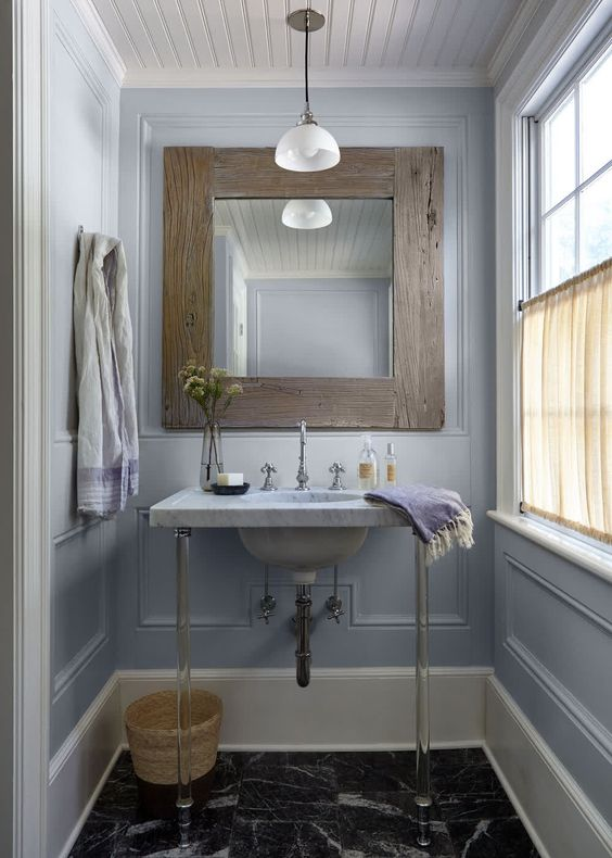 a lovely powder room clad with lilac panels, a console sink, a mirror in a wide wooden frame, a pendant lamp and pretty lilac towels