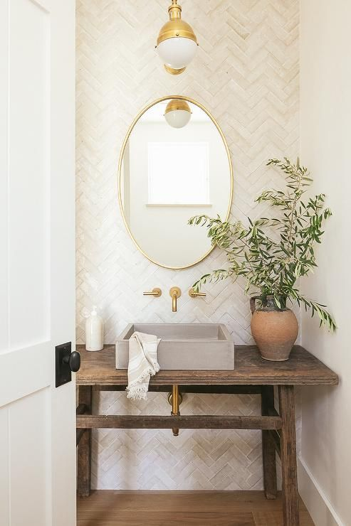 a lovely powder room with a wooden table vanity, a square concrete vessel sink, an oval mirror in a gold frame and gold touches