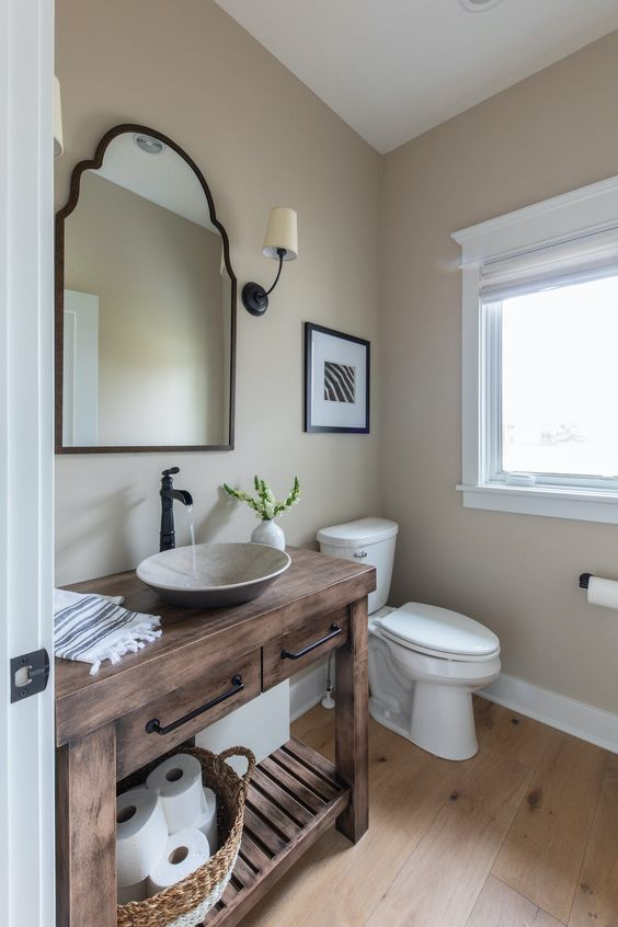 a lovely rustic powder room with a wooden vanity, a stone vessel sink, a mirror in a metal frame, tan walls and white appliances