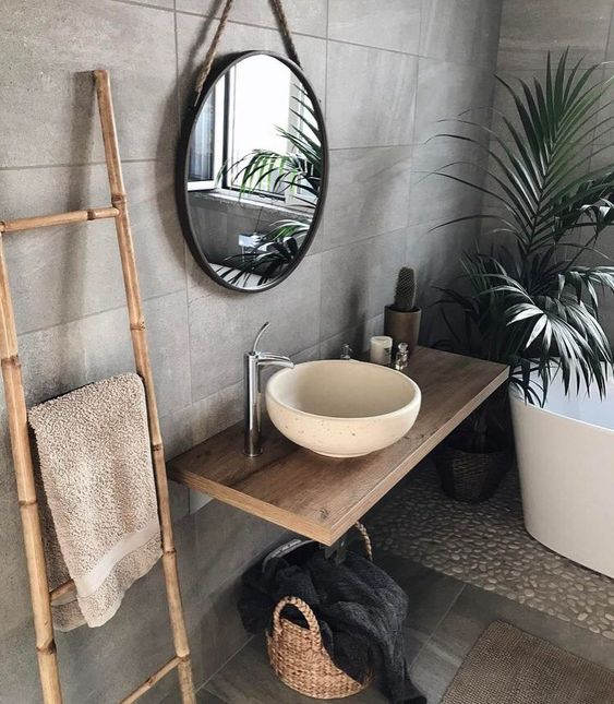 a lovely tropical bathroom clad with concrete tiles, pebbles, an oval tub, a floating vanity and a white stone vessel sink and a round mirror