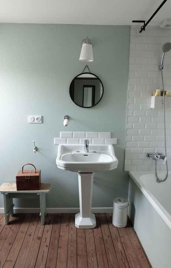 a lovely vintage bathroom with green walls, a bathtub with subway tiles around, a vintage pedestal sink with subway tiles, a round mirror, a mini stool and a chest for storage