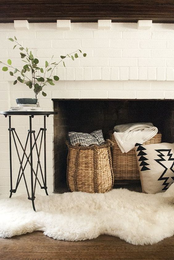 a lovely white brick fireplace with a dark stained mantel with baskets for storing blankets and pillows and a faux fur rug
