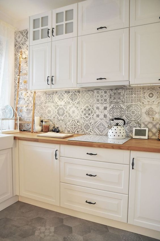 a lovely white cottage kitchen with shaker cabinets, butcherblock countertops, a black and white Moroccan tile backsplash