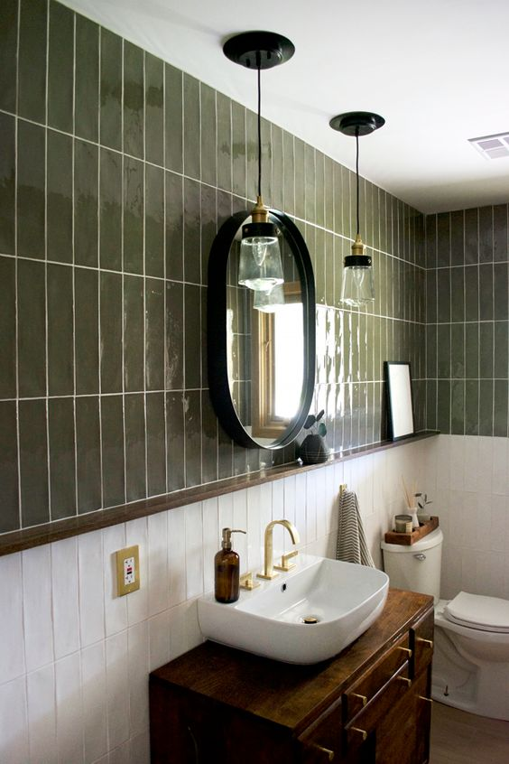 a mid-century modern bathroom with dark green and white skinny tiles, a dark stained vanity, a rounded vessel sink and an oval mirror