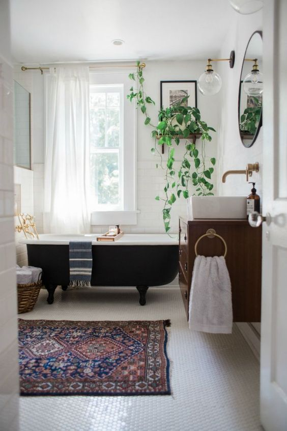 a mid-century modern bathroom with white subway tiles and penny ones, with a black clawfoot tub, a floating vanity and potted plants