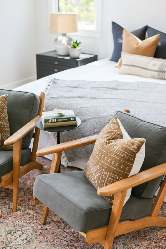 a mid-century modern bedroom with a neutral bed, bold bedding, grey chairs, black nightstands and table lamps