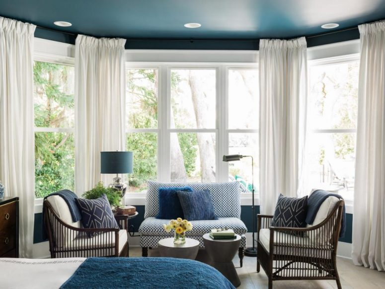 a stylish blue bedroom design with a seating area