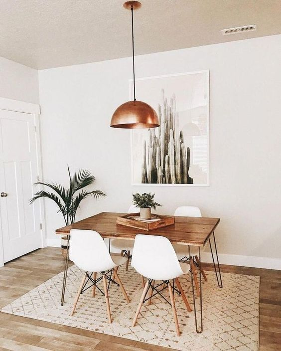 a mid-century modern dining space with a hairpin leg table, white chairs, a copper pendant lamp, potted plants and a cool boho rug