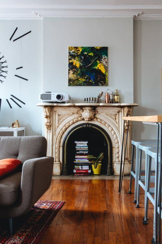 a mid-century modern living room with grey walls, a grey sofa, a vintage fireplace with a carved mantel, books and a plant inside it