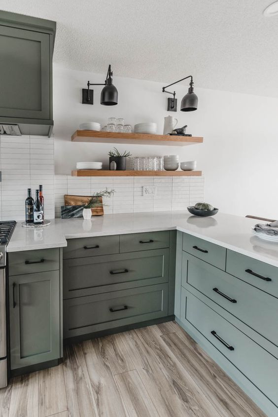 a mid-century modern olive green kitchen with shaker cabinets and black fixtures, with white stone countertops and a white skinny tile backsplash, open shelves