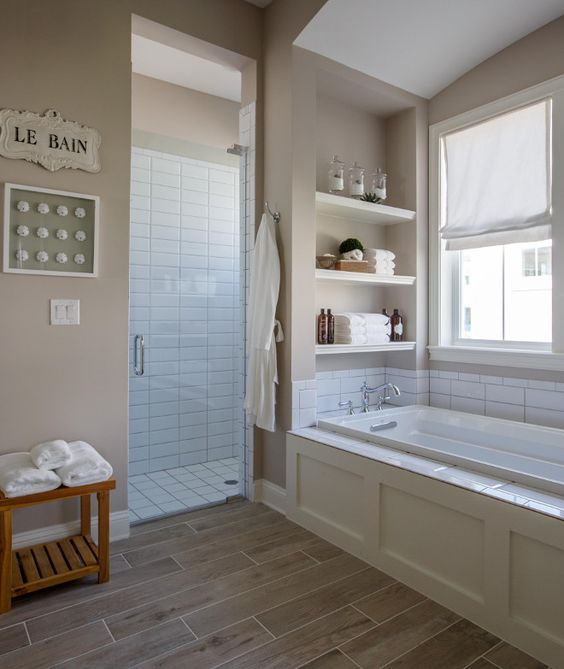 a mid-century modern tan bathroom with tan walls, wood look tiles on the floor, built-in shelves and white subway tiles