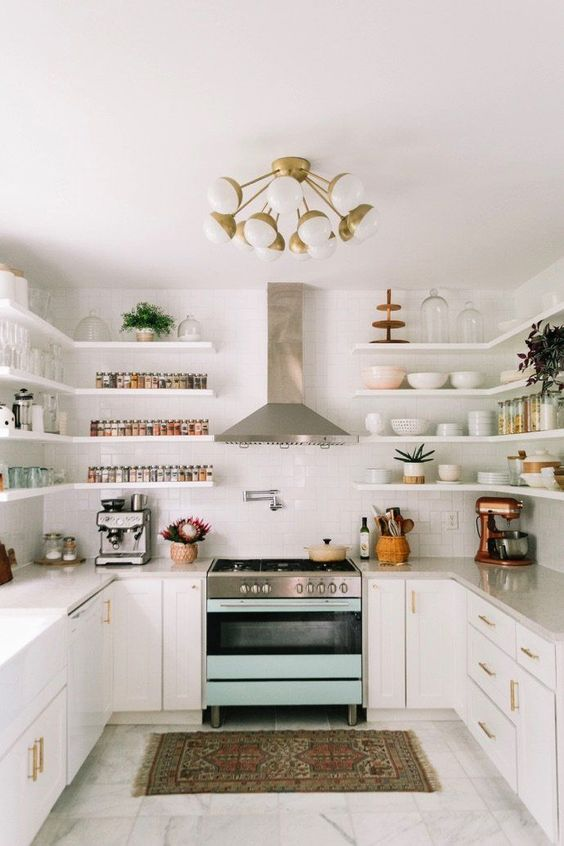 a mid-century modern white kitchen with shaker style cabinets and long floating shelves that substitute upper cabinets