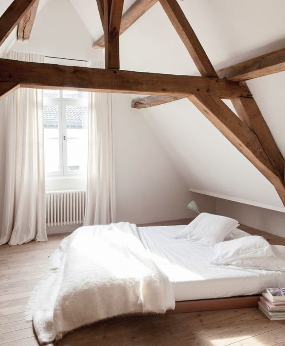 a minimal bedroom with rich-stained wooden beams, a stained low bed and neutral textiles is a very fresh idea