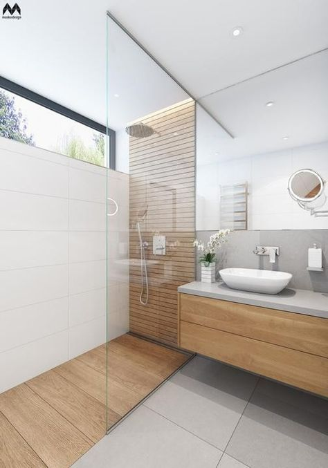a minimalist and light-filled bathroom clad with grey largre scale tiles and wood look ones, a wooden vanity, a sink, a mirror and a small skylight