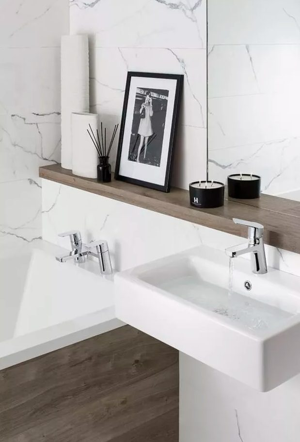 a minimalist bathroom clad with white stone tiles, a bathtub clad with wood, a wooden shelf and a small floating sink for a chic look