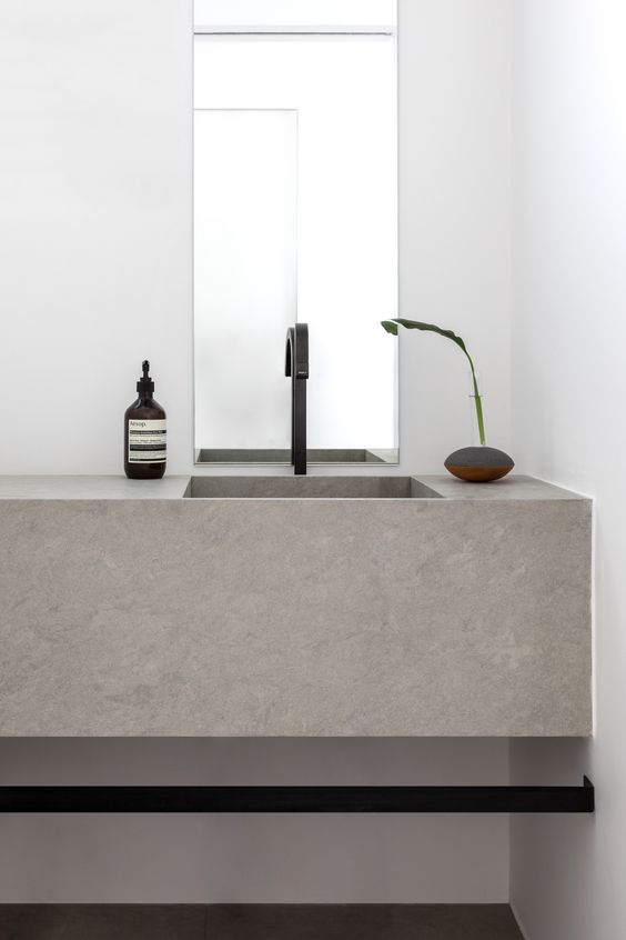a minimalist bathroom in neutrals, with a concrete slab floating sink, black fixtures and a very laconic mirror is a very stylish idea to go for