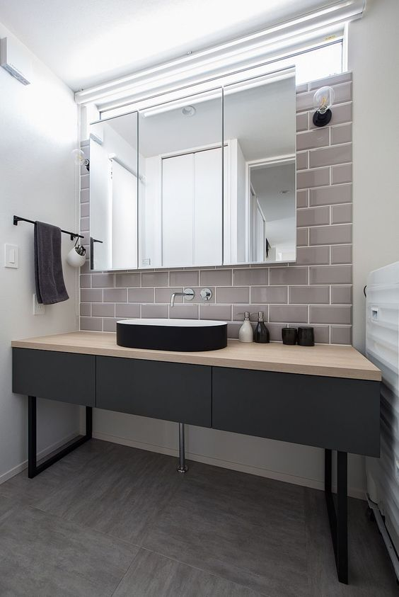 a minimalist bathroom with a matte black vanity, a sleek black vessel sink, a large mirror cabinet and a grey subway tile accent wall