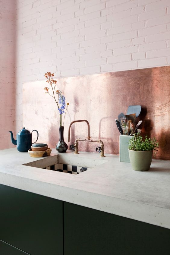 a minimalist dark green kitchen with a thick concrete countertop and a copper backsplash is a lovely and bold idea to rock