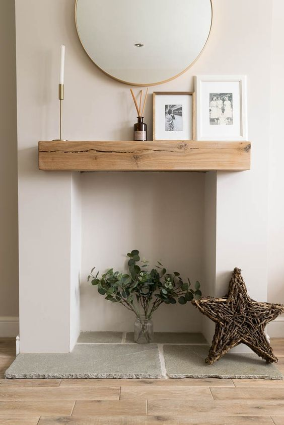 a minimalist faux fireplace with a wood slab mantel, a twi star, a vase with eucalyptus in the fireplace, some art and a round mirror