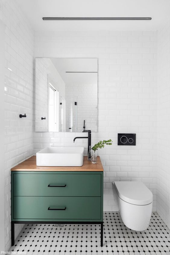 a modern and serene powder room clad with white subway tiles, with a green and black vanity, a square vessel sink, white appliances and a large mirror