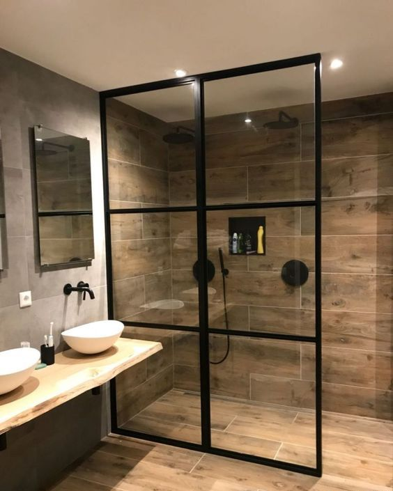 a modern bathroom clad with grey and wood look tiles, with black fixtures, bowl sinks, a framed shower wall is a cool and cozy space