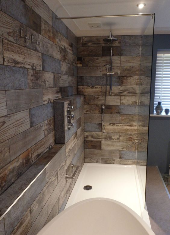 a modern bathroom clad with reclaimed wood look tiles, with white appliances and built-in lights is a stylish and cool idea