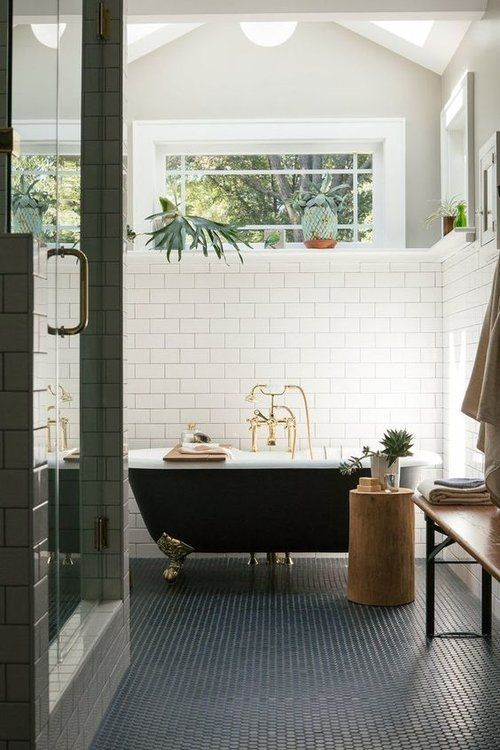 a modern bathroom clad with white subway and penny tiles, a vintage black bathtub, a shower, a bench and a tree stump side table