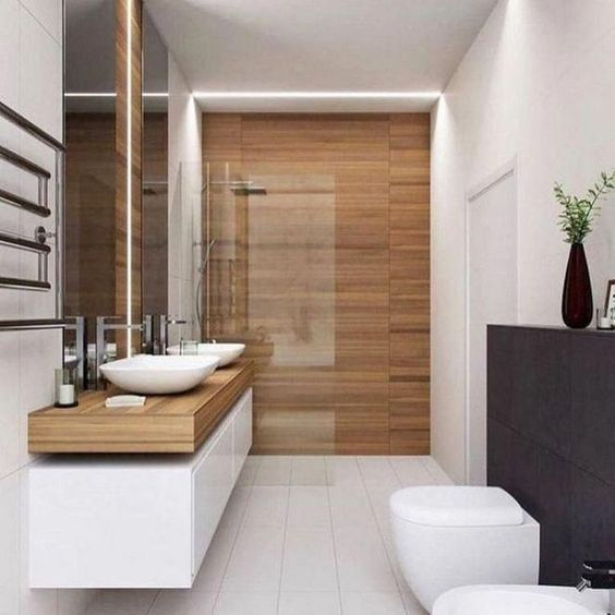 a modern bathroom clad with wood look and neutral tiles, with a long double vanity, white appliances and built-in lights