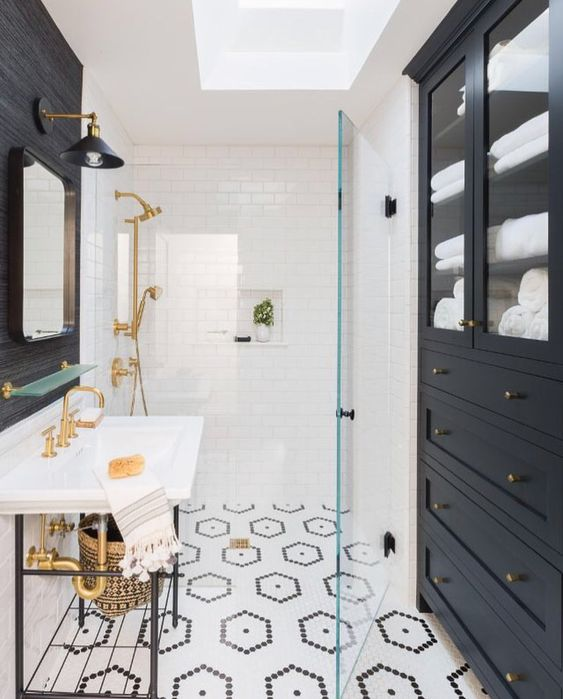 a modern bathroom with a penny tile floor, a black accent wall and a navy storage unit, a console sink and gold fixtures is cool