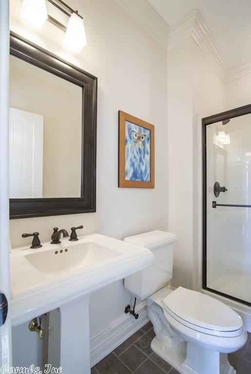 a modern bathroom with a shower space, a pedestal sink, a mirror in a black frame, a bold artwork and black fixtures for more contrasting looks
