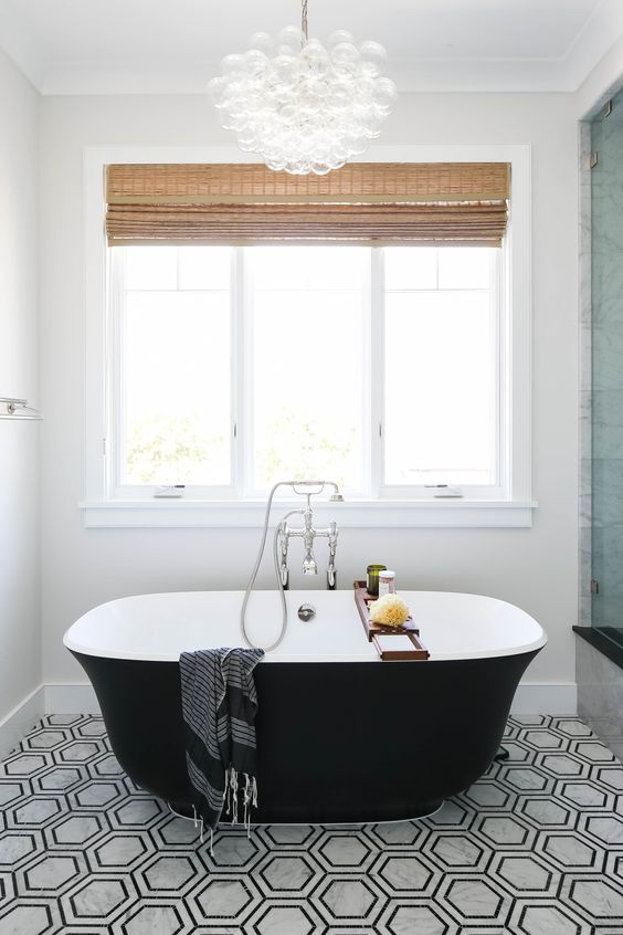 a modern bathroom with black and white hex tiles, a small black tub and a shower space, shades and a bubble chandelier