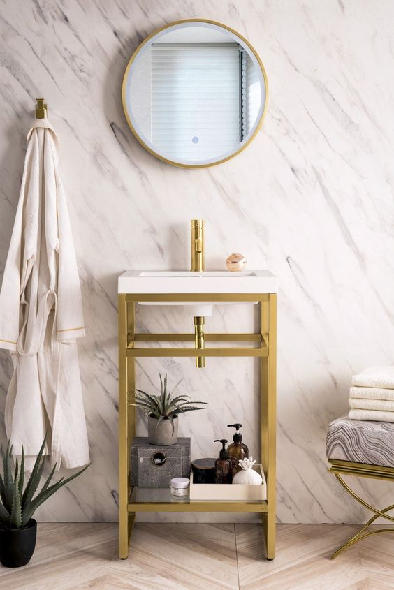 a modern bathroom with stone-imitating wallpaper, a chevron wooden floor, a console sink, a round mirror in a gold frame