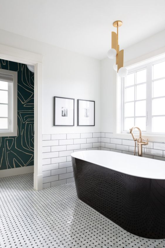 a modern bathroom with two different types of tiles, a sleek black clad tub, a catchy pendant lamp and pritned wallpaper