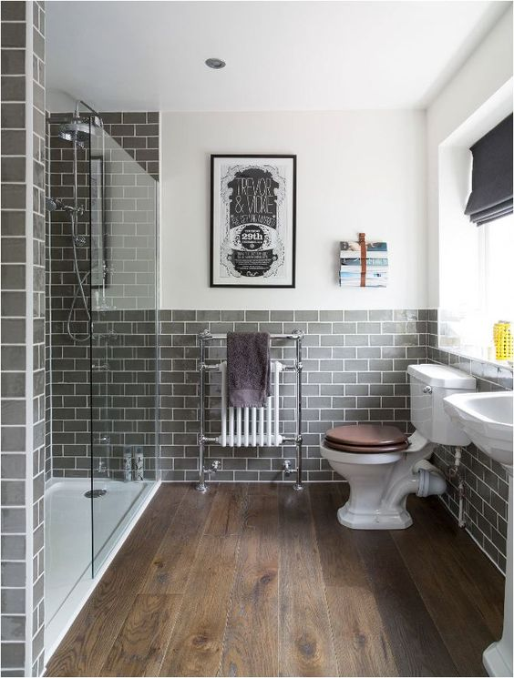 a modern bathroom with wood look tiles on the floor and grey subway tiles on the walls, white vintage appliances and a bold poster