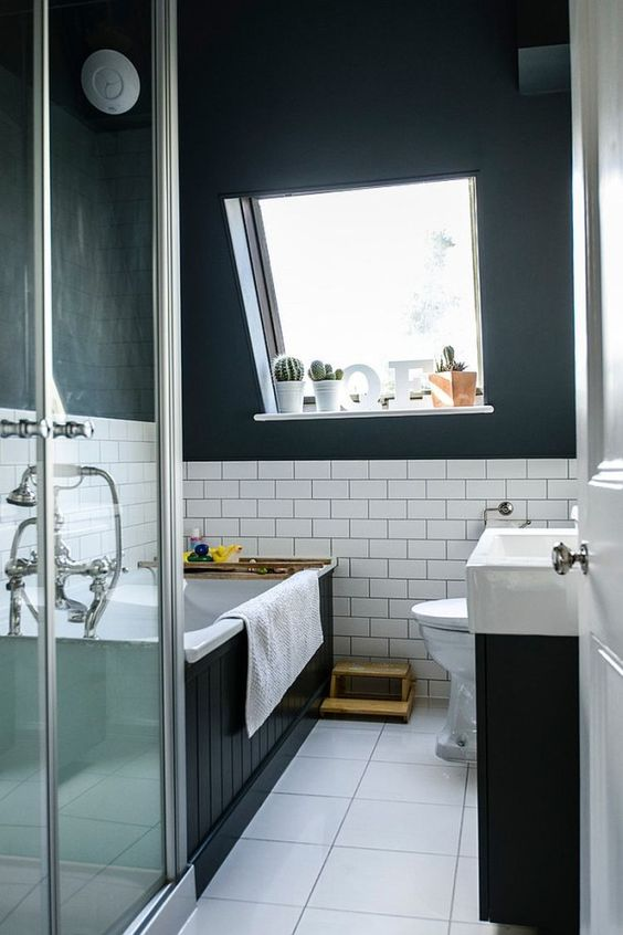 a modern black and white attic bathroom with a bathtub clad with black palnks, a black vanity with a white sink, a square tile floor