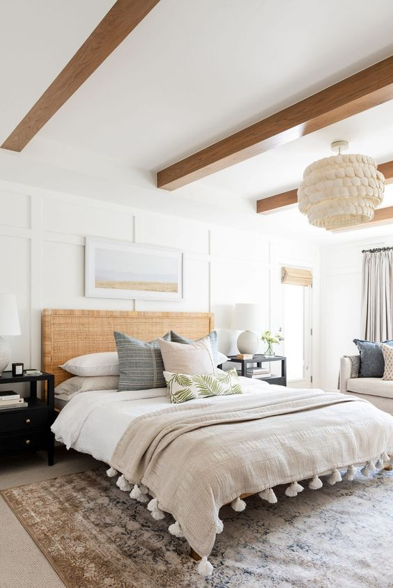 a modern coastal bedroom with stained wooden beams, a bed with a rattan headboard, neutral bedding, black nightstands, neutral bedding