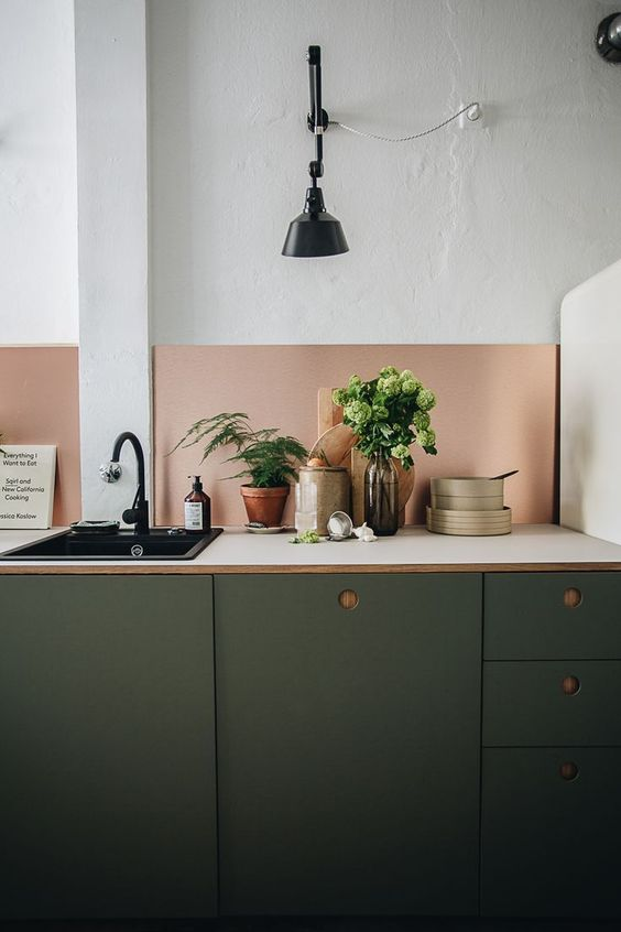 a modern dark green kitchen with white countertops, a copper backsplash and black fixtures is a stylish idea and the colors look great with each other