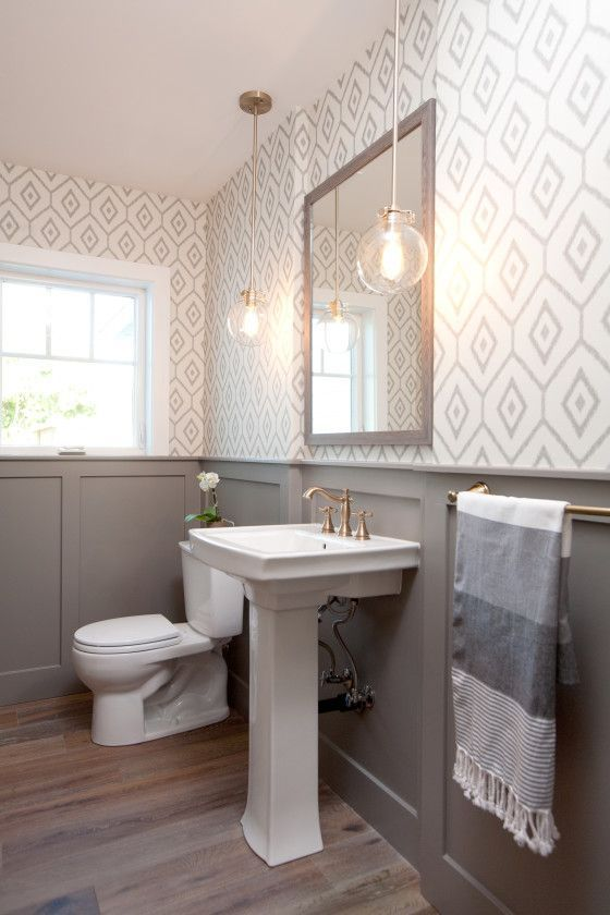 a modern farmhouse bathroom with geo wallpaper, grey paneling, a pedestal sink, a mirror in a wooden frame and pendant lamps