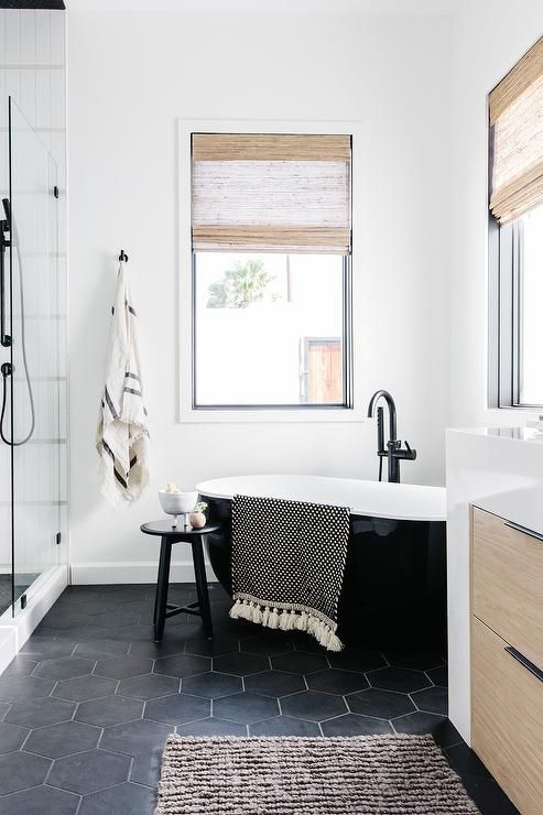 a modern farmhouse bathroom with white and black hex tiles, with a sleek and shiny black tub, a shower, a stool and a light-stained vanity