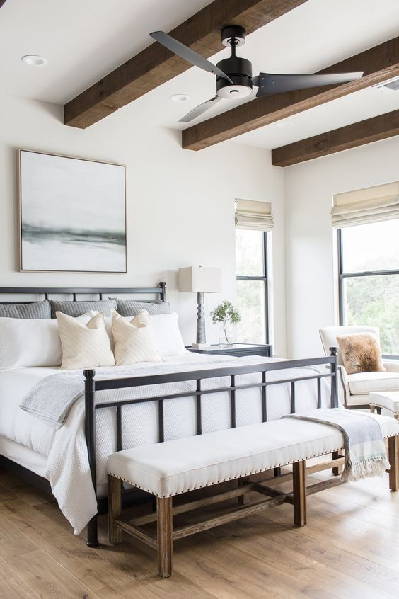 a modern farmhouse bedroom with a black forged bed, a neutral upholstered bench, wooden beams and neutral chairs